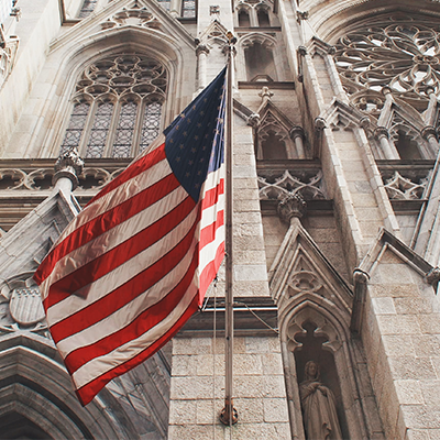 An American flag flying outside of a cathedral. Photo credit: https://unsplash.com/@stepanvrany