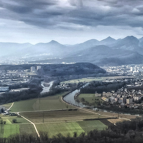 Many buildings in a valley with mountains in the background, and a river and roads across the landscape. Crop of a photo by Patrick Federi, via unsplash.